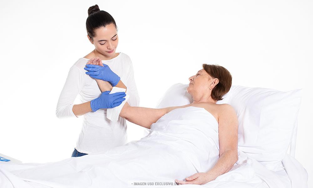 Enfermera seca a un paciente con una toalla desechable